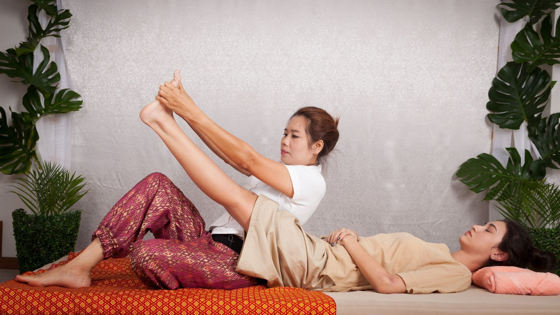 A woman giving another woman a Thai massage.