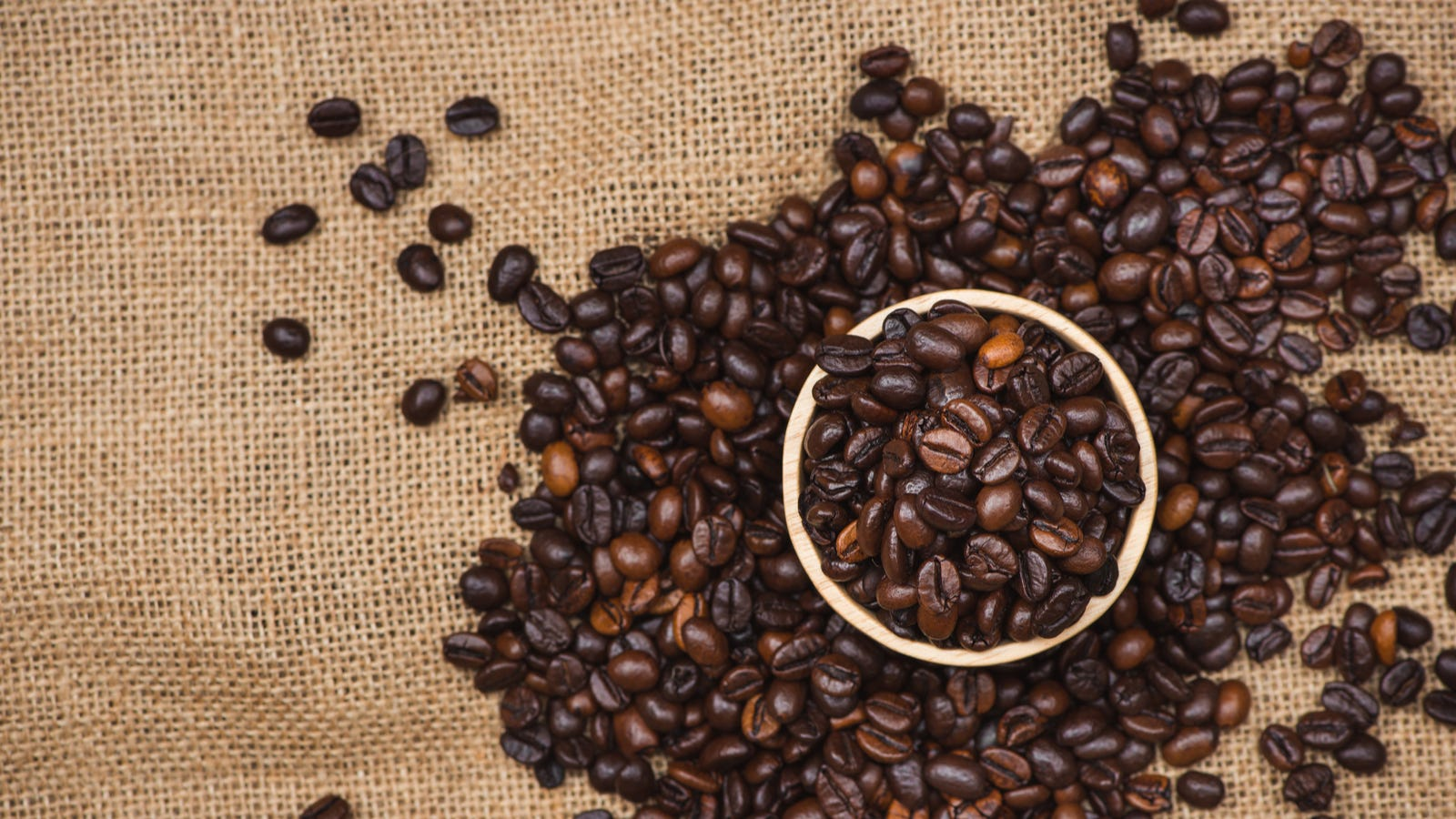 A cup overflowing with roasted coffee beans over a canvas background.