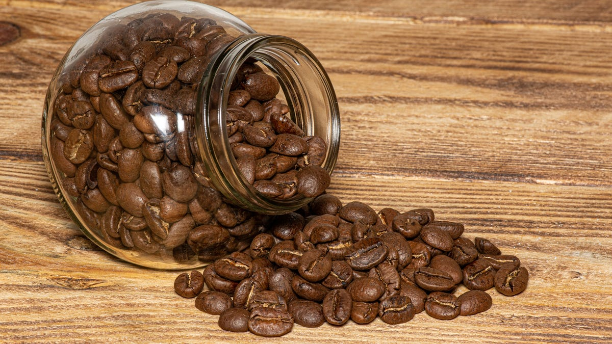 Coffee beans spill out of a glass jar and onto a wooden table
