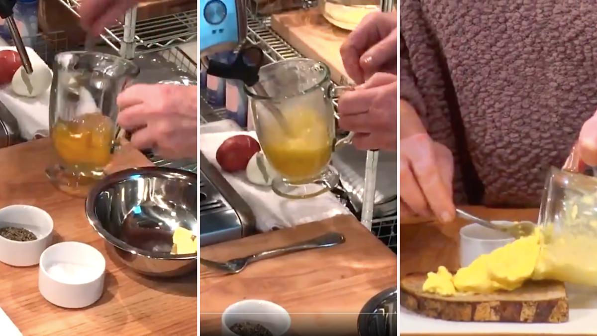 A person scrambles eggs in a glass mug using a milk steamer.