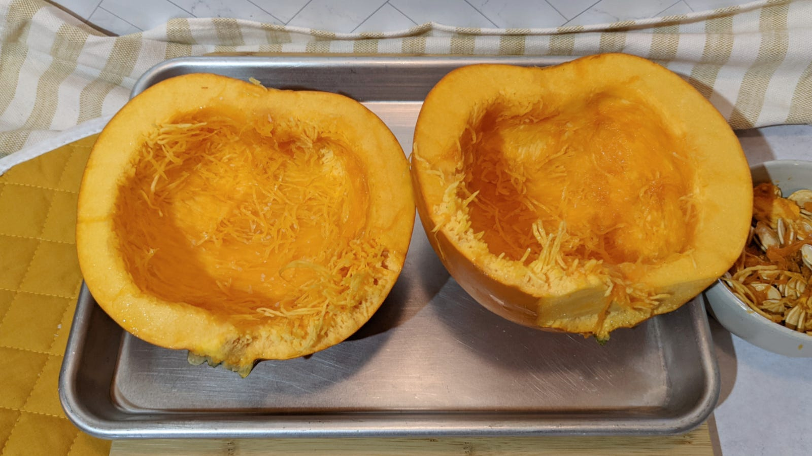 A halved sugar pumpkin with oil massaged on the inside, placed on a sheet tray before going in the oven.