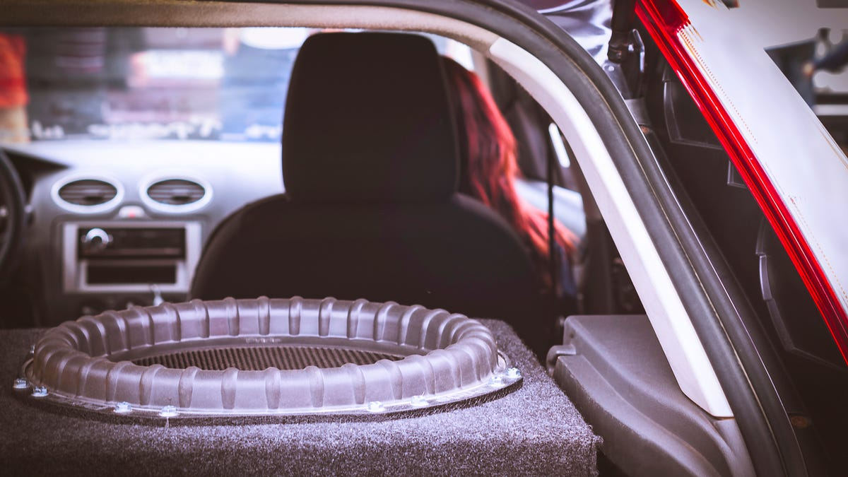 A large subwoofer in the back of a car with a redheaded woman sitting in the passenger seat.