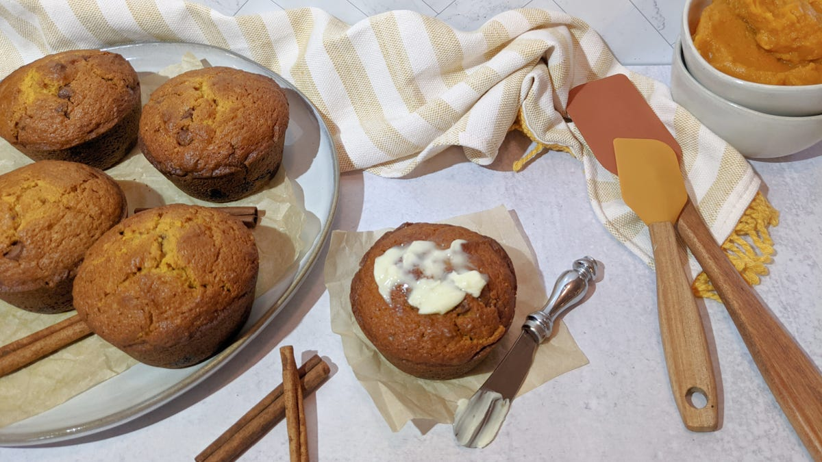A warm muffin with butter melting over the top, placed along side of a dish filled with warm muffins, a few scraper spatulas and some purred pumpkin in the background.