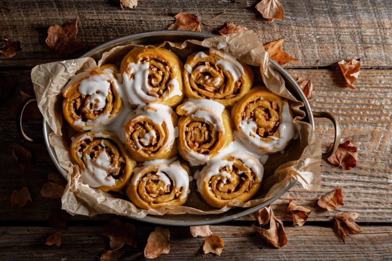 A pan of pumpkin cinnamon rolls sitting on a wooden board