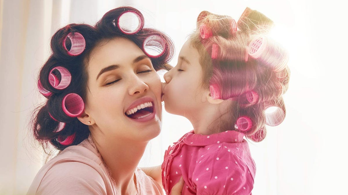 A young daughter kisses her mom's cheeks with both of them wearing hair rollers.