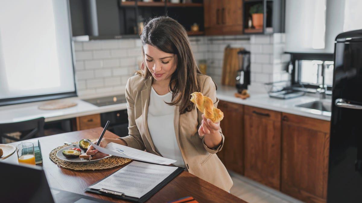 Uma mulher toma café da manhã enquanto trabalha.