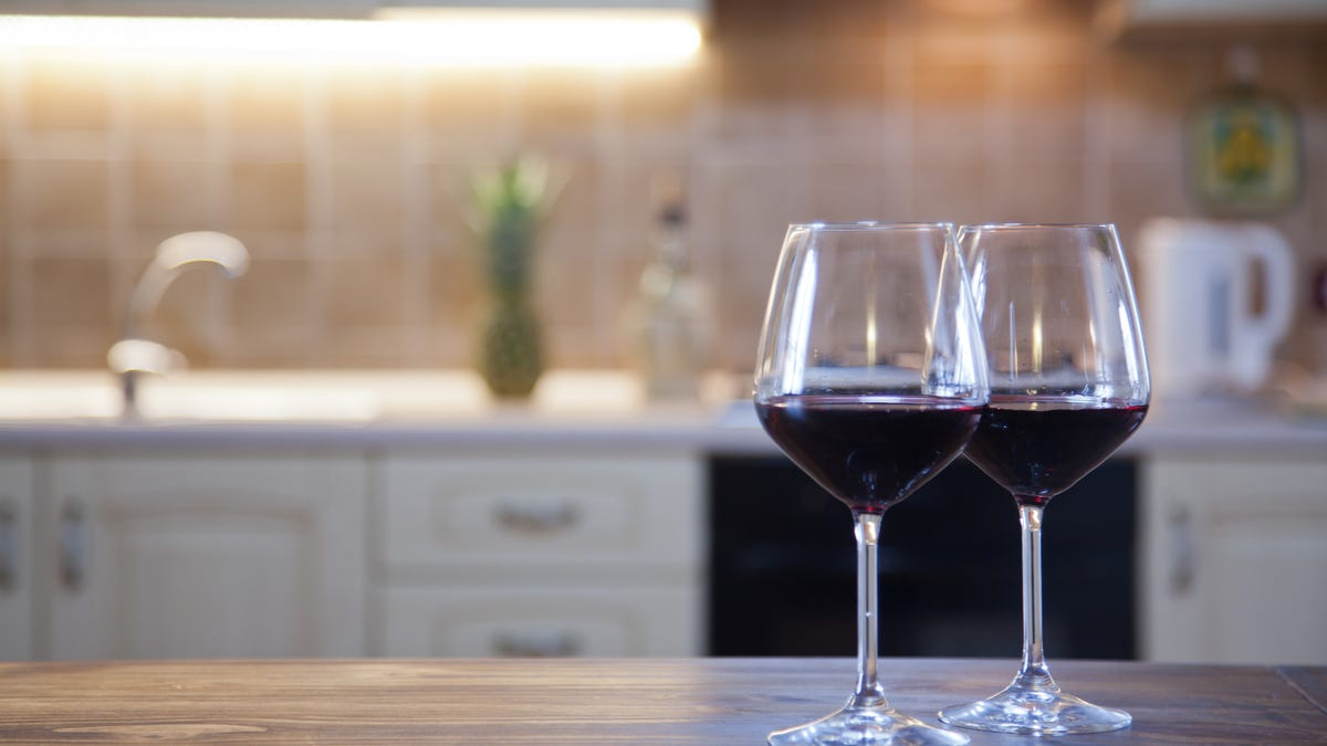 Two wine glasses sit on a kitchen counter