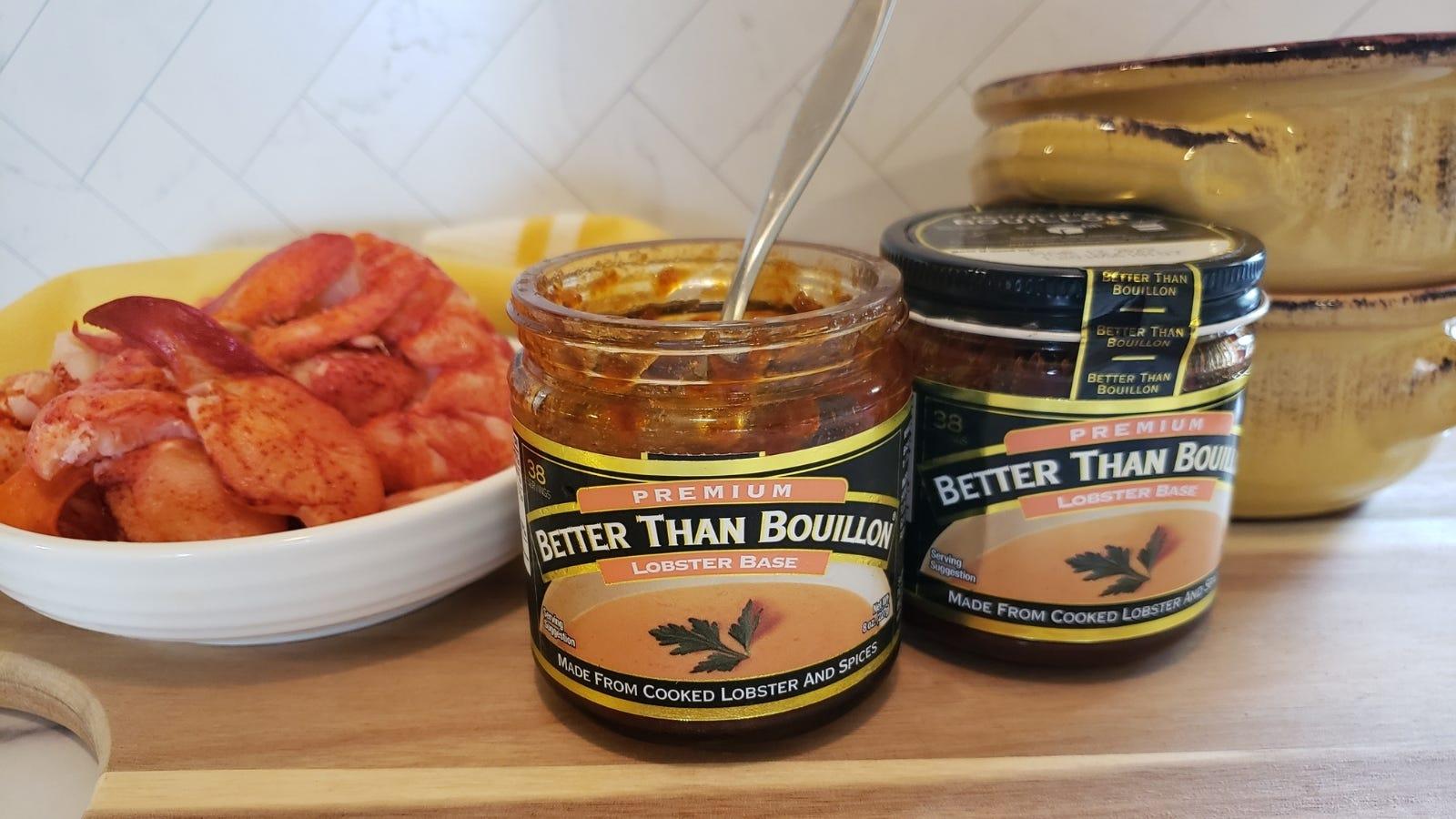 Two jars of Better than Bouillon lobster base presented with two crocks and a shallow dish of lobster meat in the background.