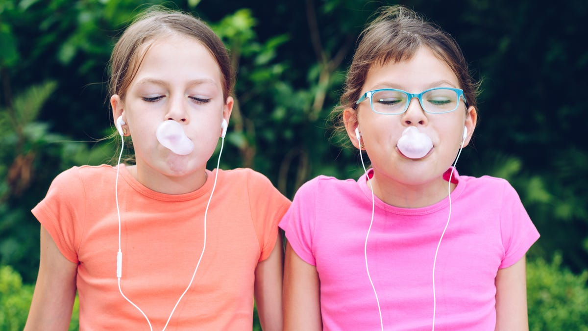 Two girls blow bubbles with gum.