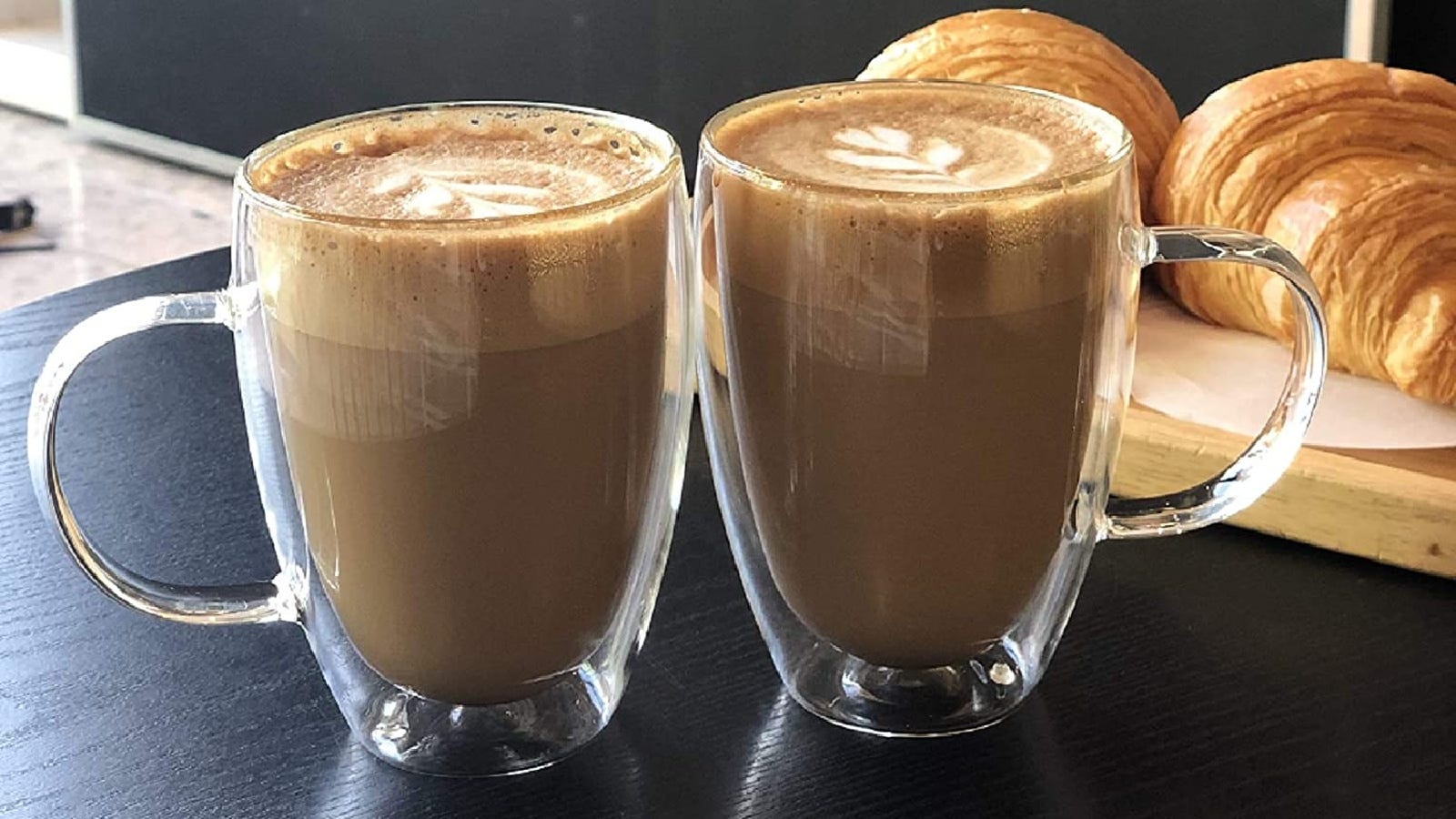 Two tall double walled latte glass mugs filled with lattes with croisants in the background.