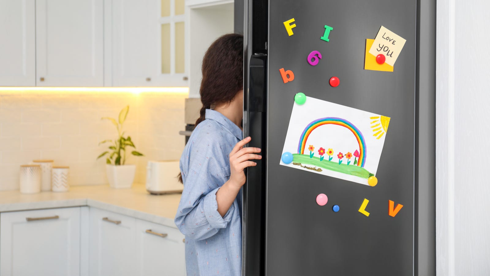 A woman opening a fridge door and grabbing something.