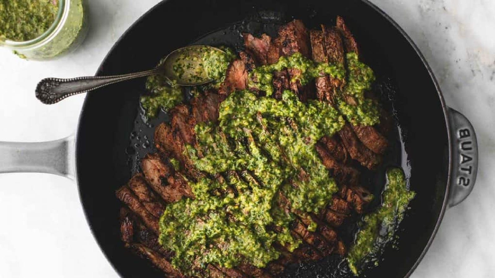 A staub enameled cast iron skillet filled flank steak, cut against the grain smothered with scratch chimmichurri sauce.