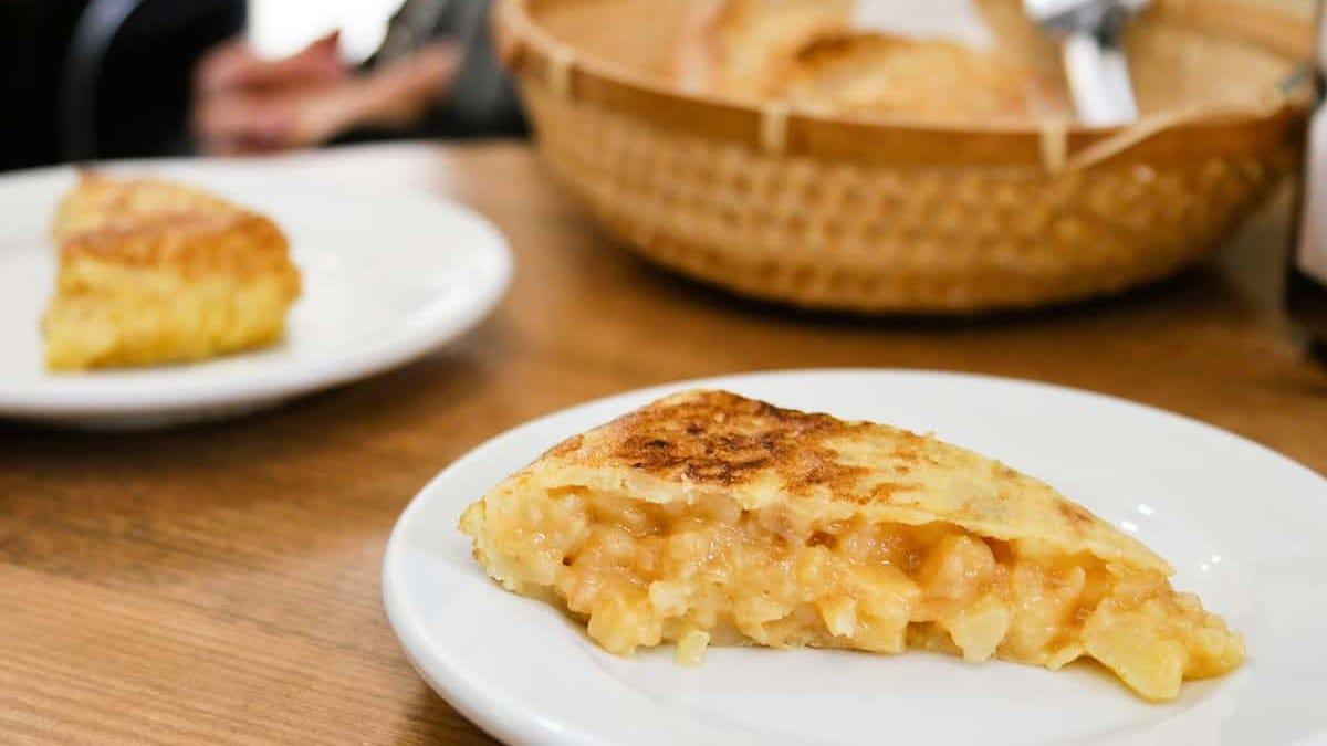 Two tortilla de patatas on plates.