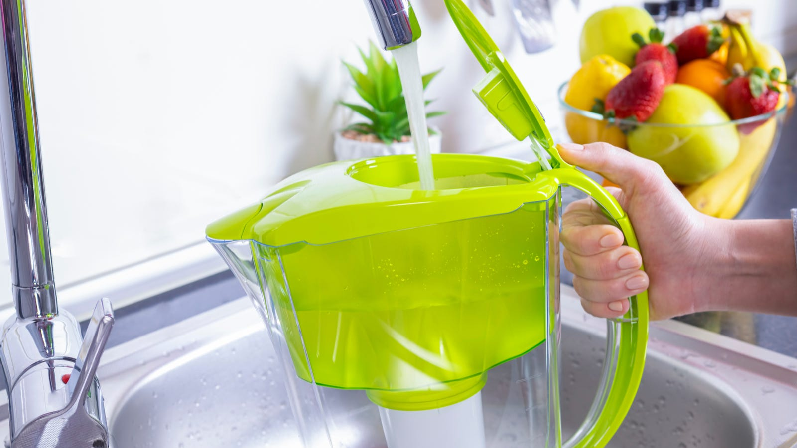 A person filling a water filter pitcher at the sink with a bowl of fruit in the background.