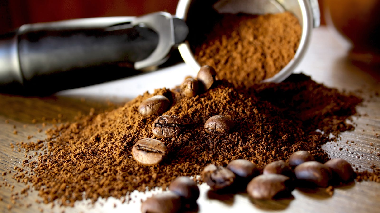 ground coffee with multple coffee beans mixed in.