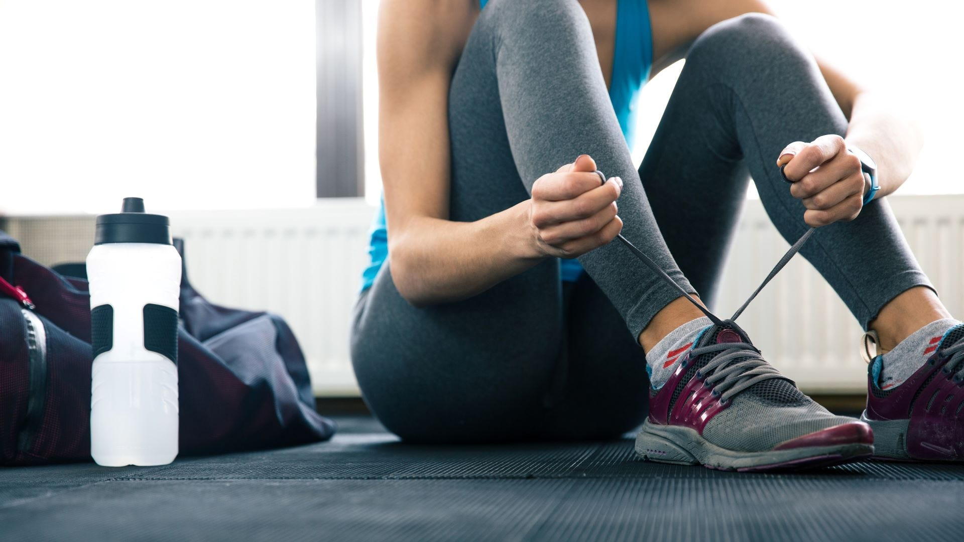 A woman tying the shoelaces on her cross-training shoes in a gym.
