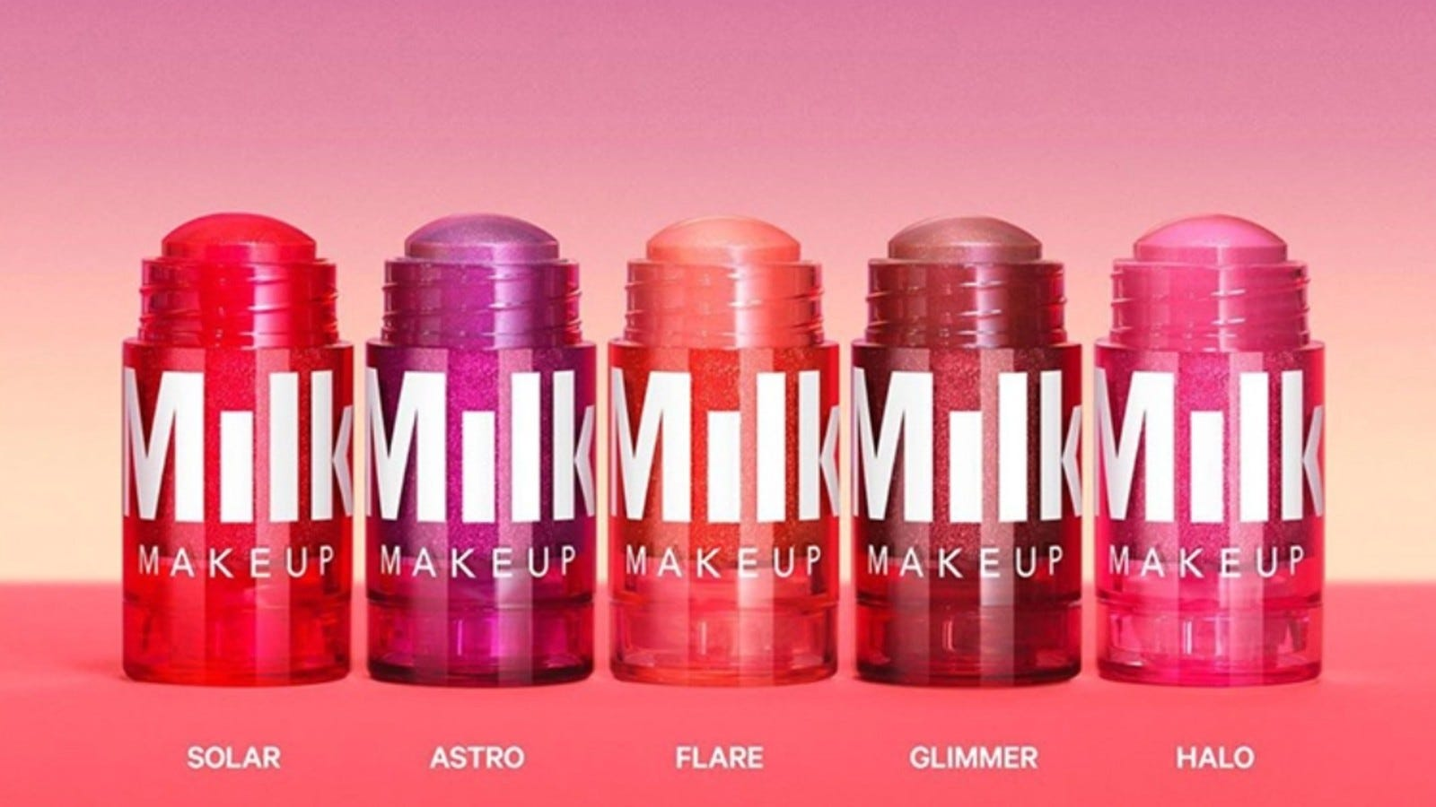 colorful Milk Makeup tubes on pink and purple background