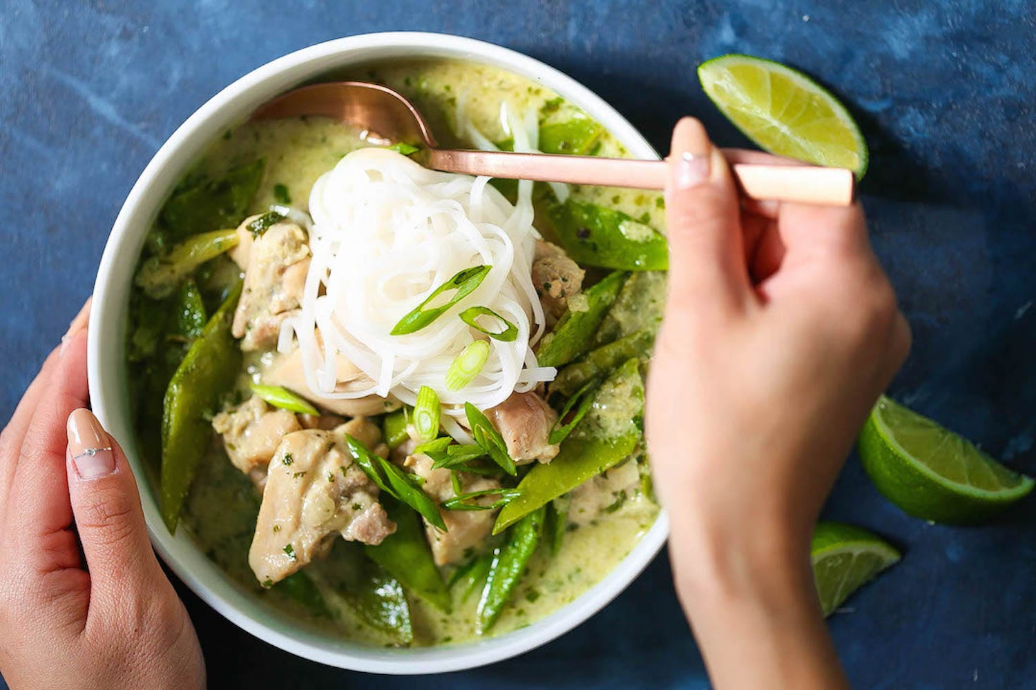 A pair of hands stirring a bowl of green curry chicken soup