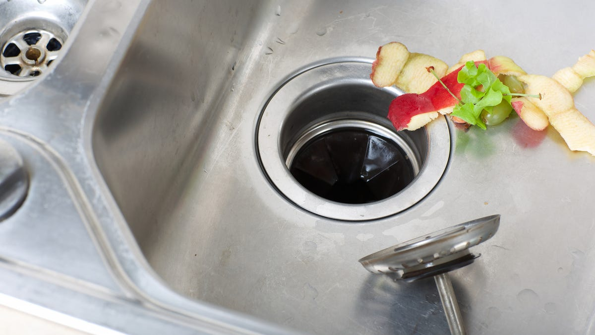 food waste sits at the edge of a garbage disposal.