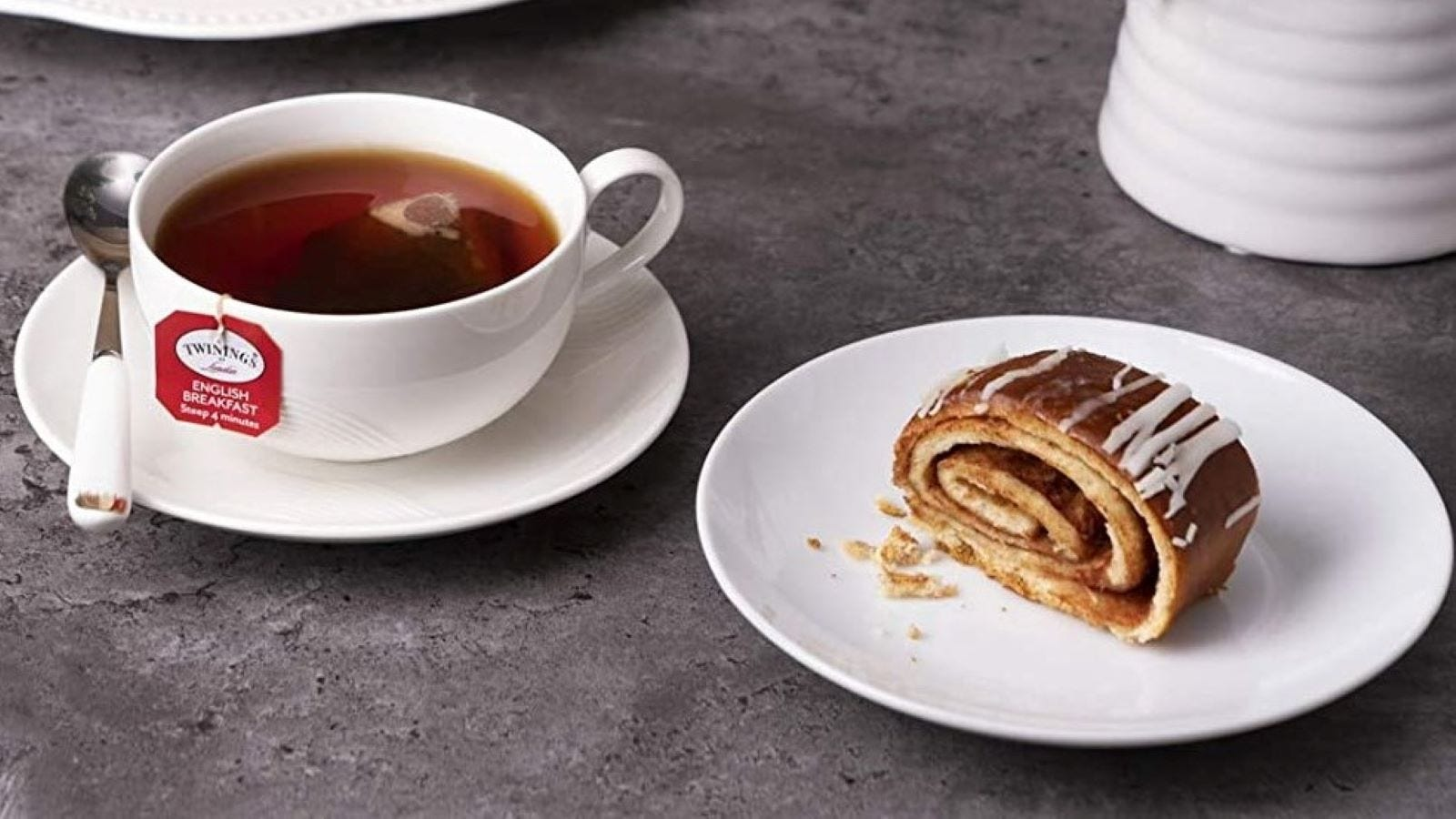 A cup of Twinings tea next to a cinnamon roll on a plate.