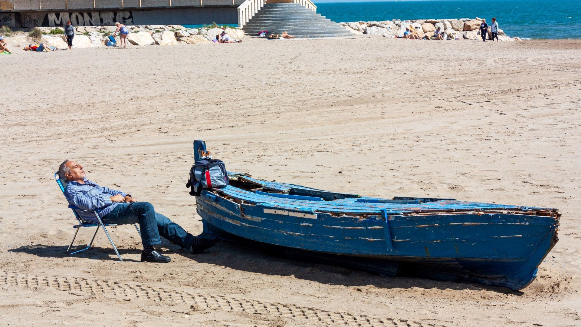 A man taking a siesta on a beach in Spain next to a boat.