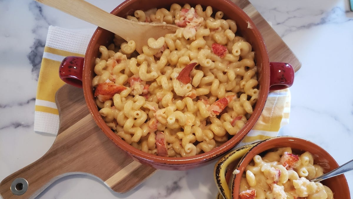 A large ceramic baking dish with two crocks filled with lboster mac and cheese.