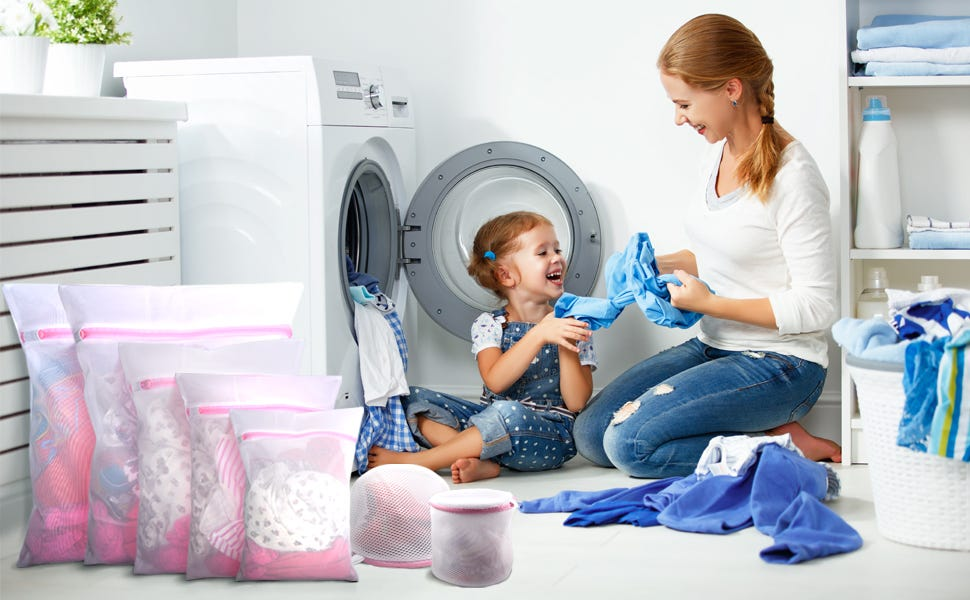 A woman and little girl taking laundry out of the dryer with seven GOGOODA mesh laundry bags full of clothes sitting next to them.