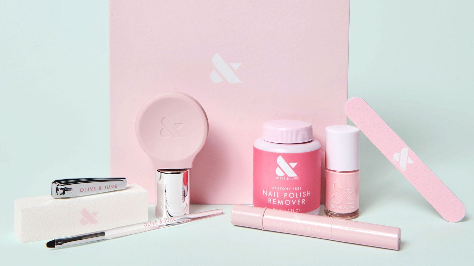 A nail file, buffer, brush, top coat, remover, cuticle serum, and polish sit in front of a box with an ampersand on it.