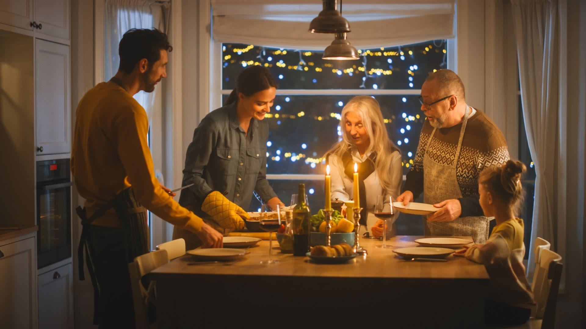 A young couple and a little girl serving an elderly couple a candlelight dinner.
