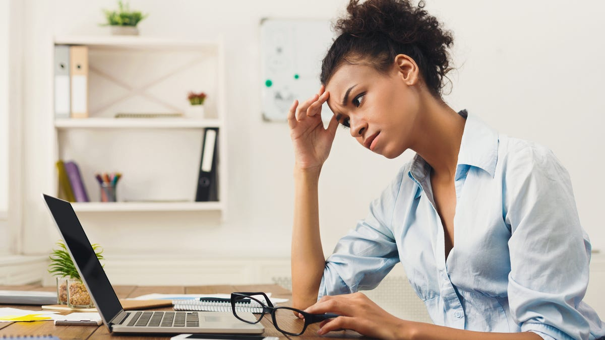 A woman furrows her brow looking at a computer