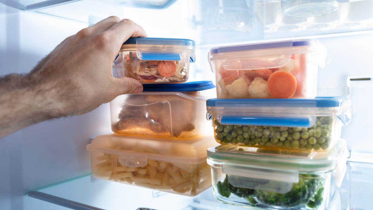 A person puts leftover containers in a freezer.
