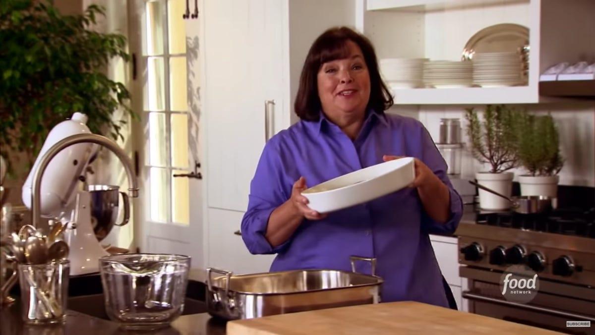 Ina Garten holds a ceramic baking pan in her hands.