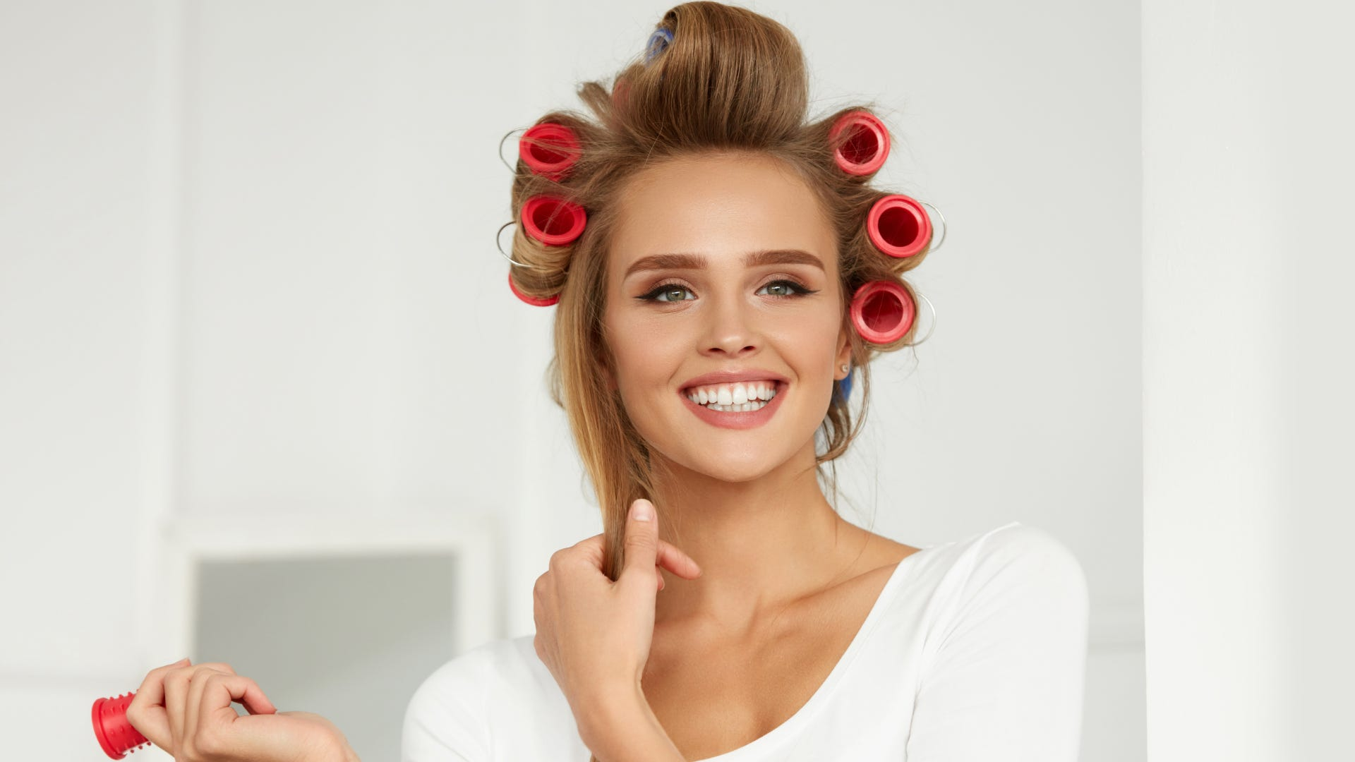 A smiling girl wears pink hair rollers on her head.