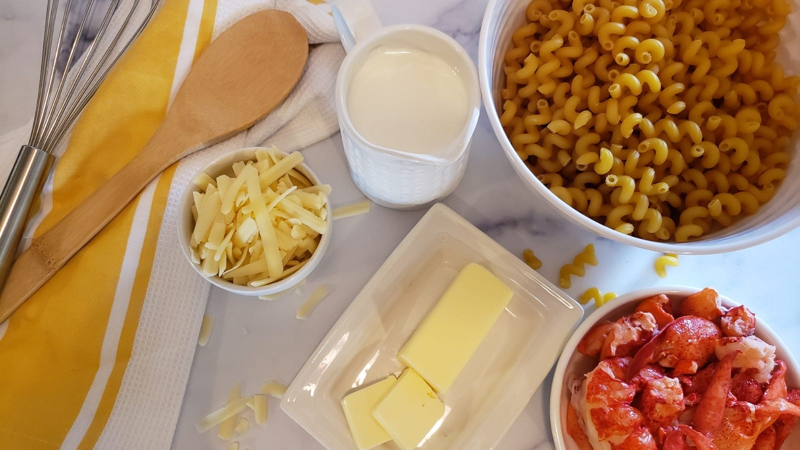 Pasta, cream, cheese, butter and lobster meat; all the ingredients and some tools needed to make lobster macaroni and cheese.