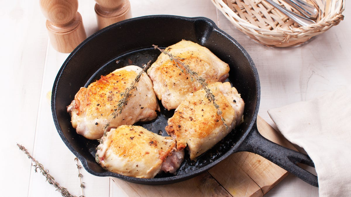 Four chicken thighs sit in a cast iron skillet.