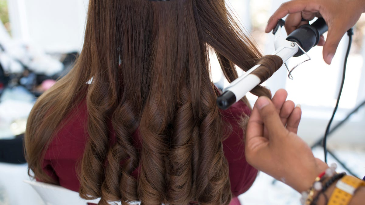 A hairstylist curls a woman's brown hair with a small-barreled curling iron.