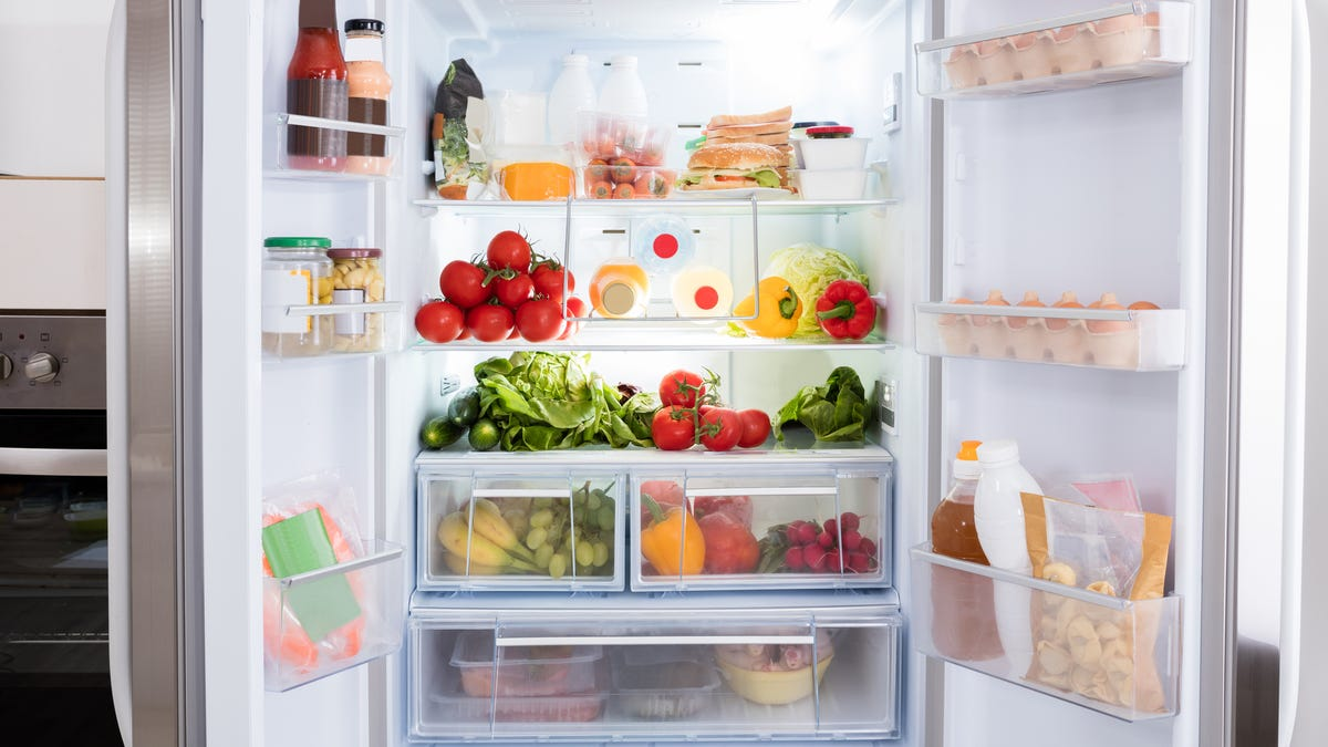 A fridge's doors are open to reveal fresh vegetables and fruit.