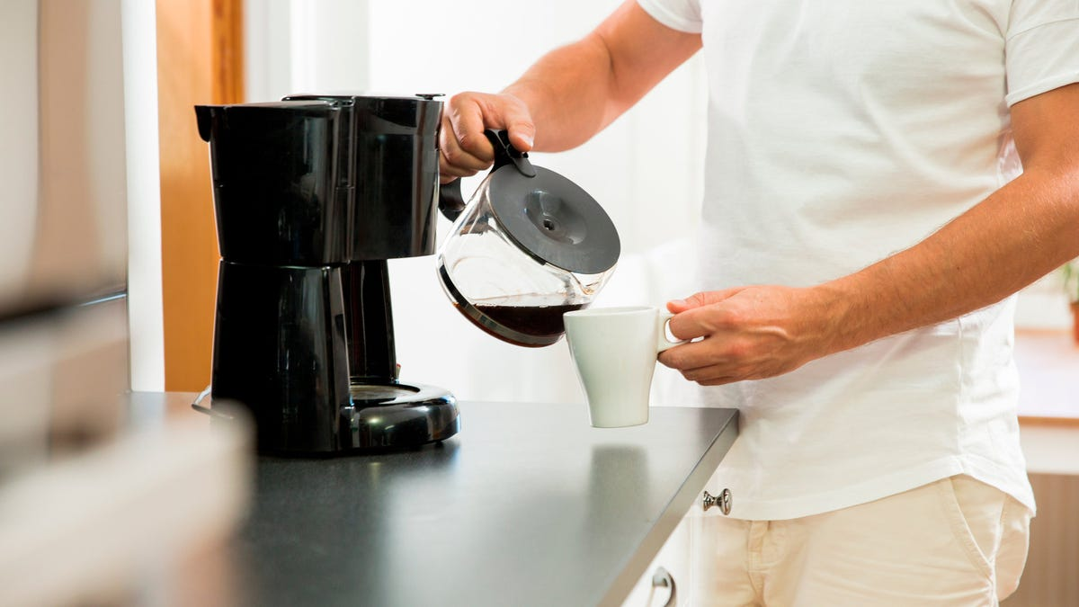 A man pouring a cup of coffee at home.