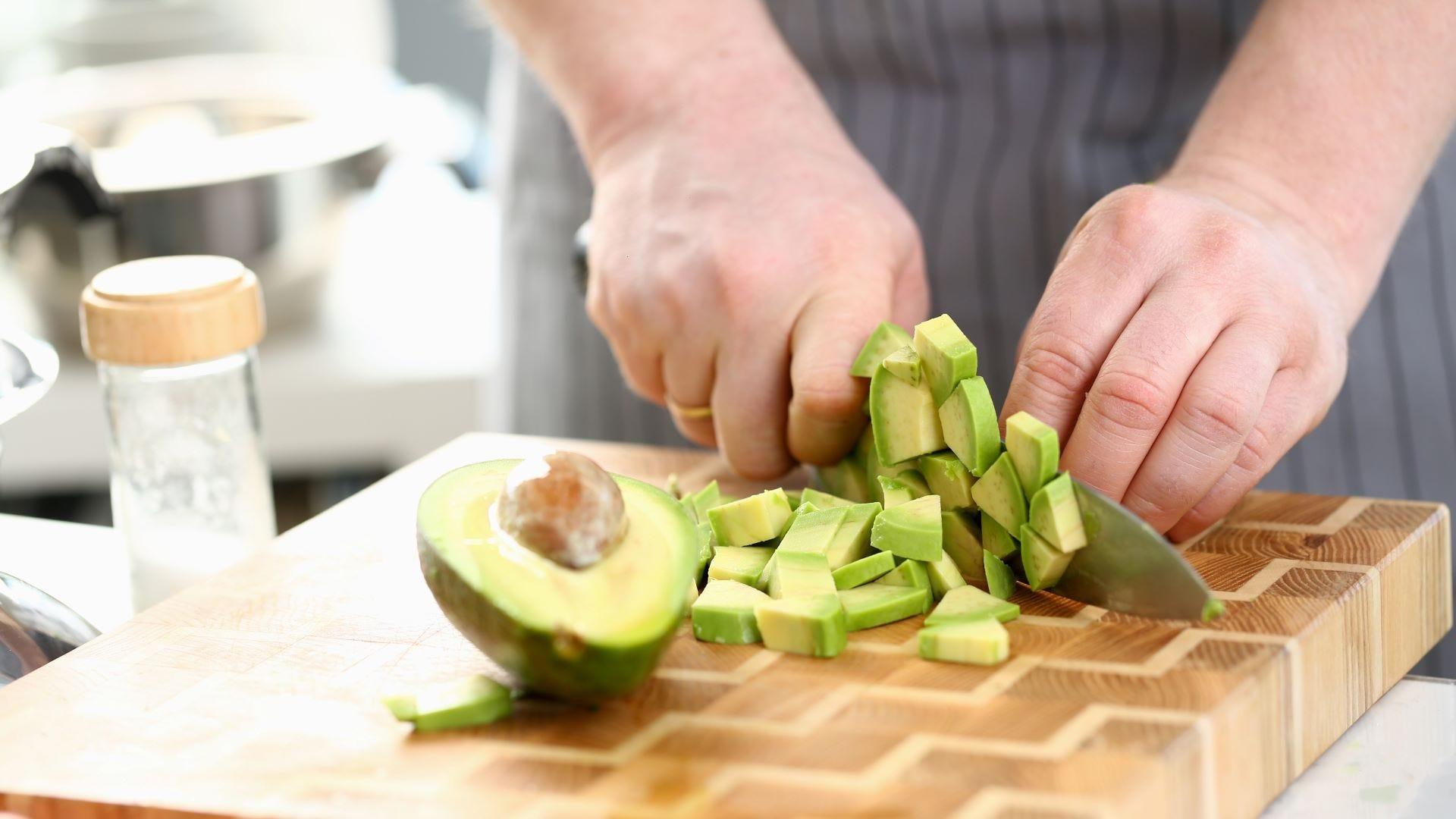 Someone slicing an avocado on a cutting board.