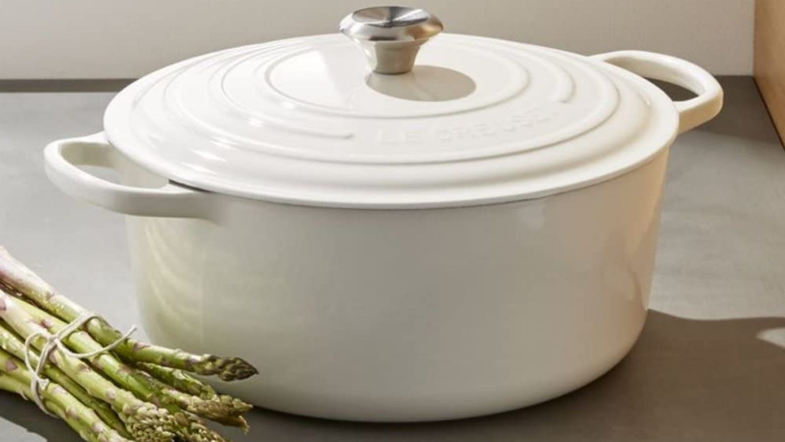 A white Le Creuset 5.5 quart Dutch oven presented with a bunch of asparagus next to it.
