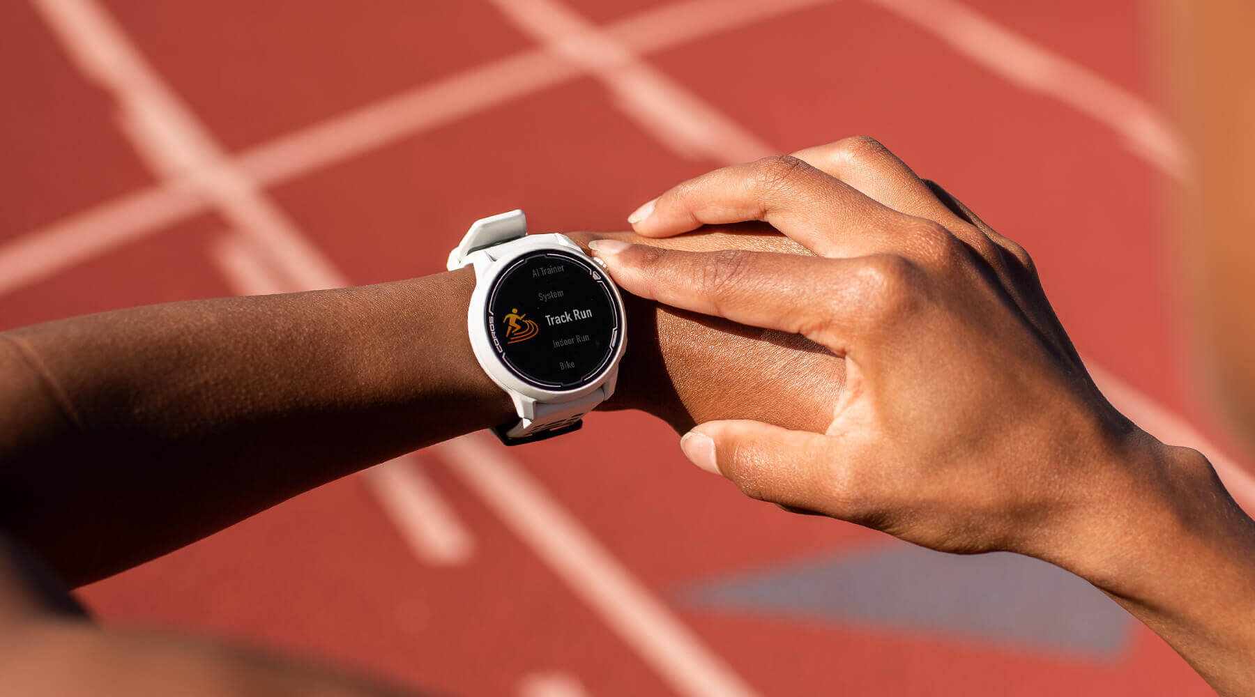 White running smartwatch on a woman's hand in front of a track field.