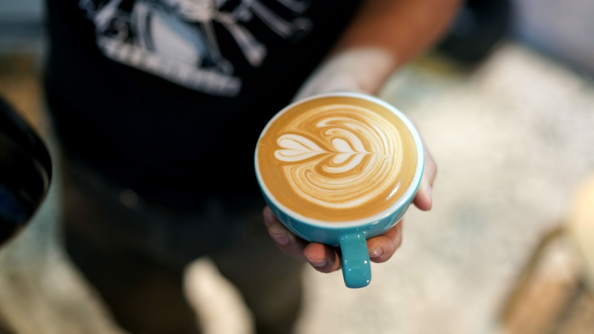 Someone holding a latte with a milk heart in a mug.