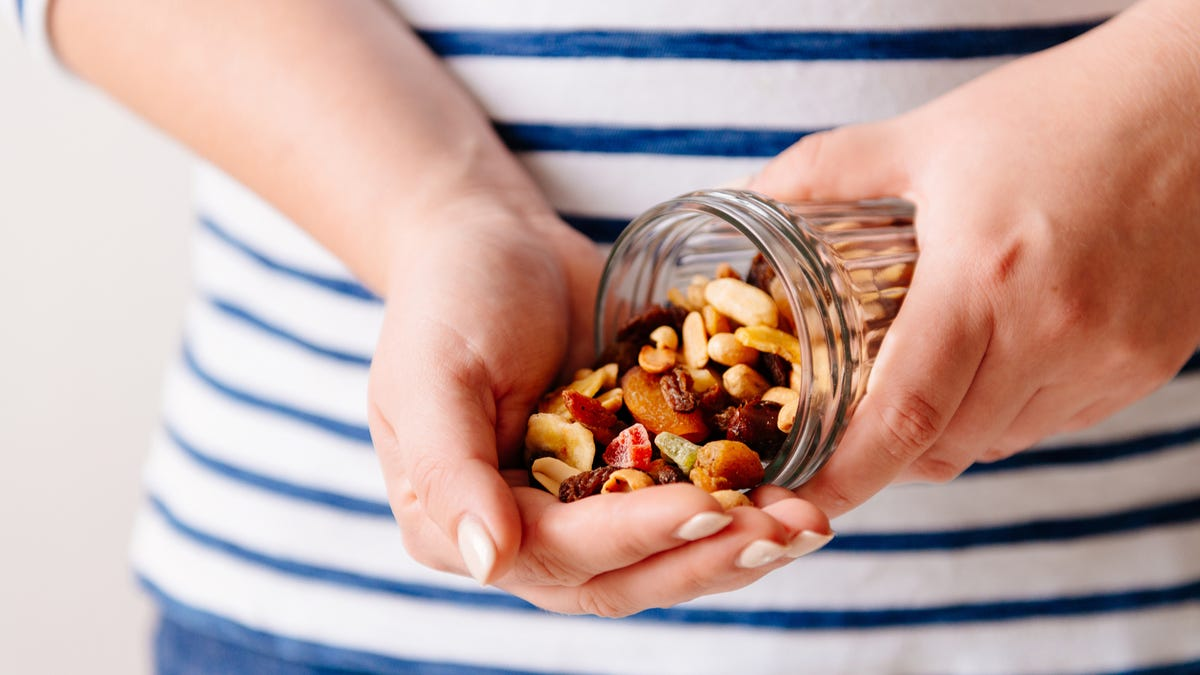 A person empties a jar of nuts into their hand.