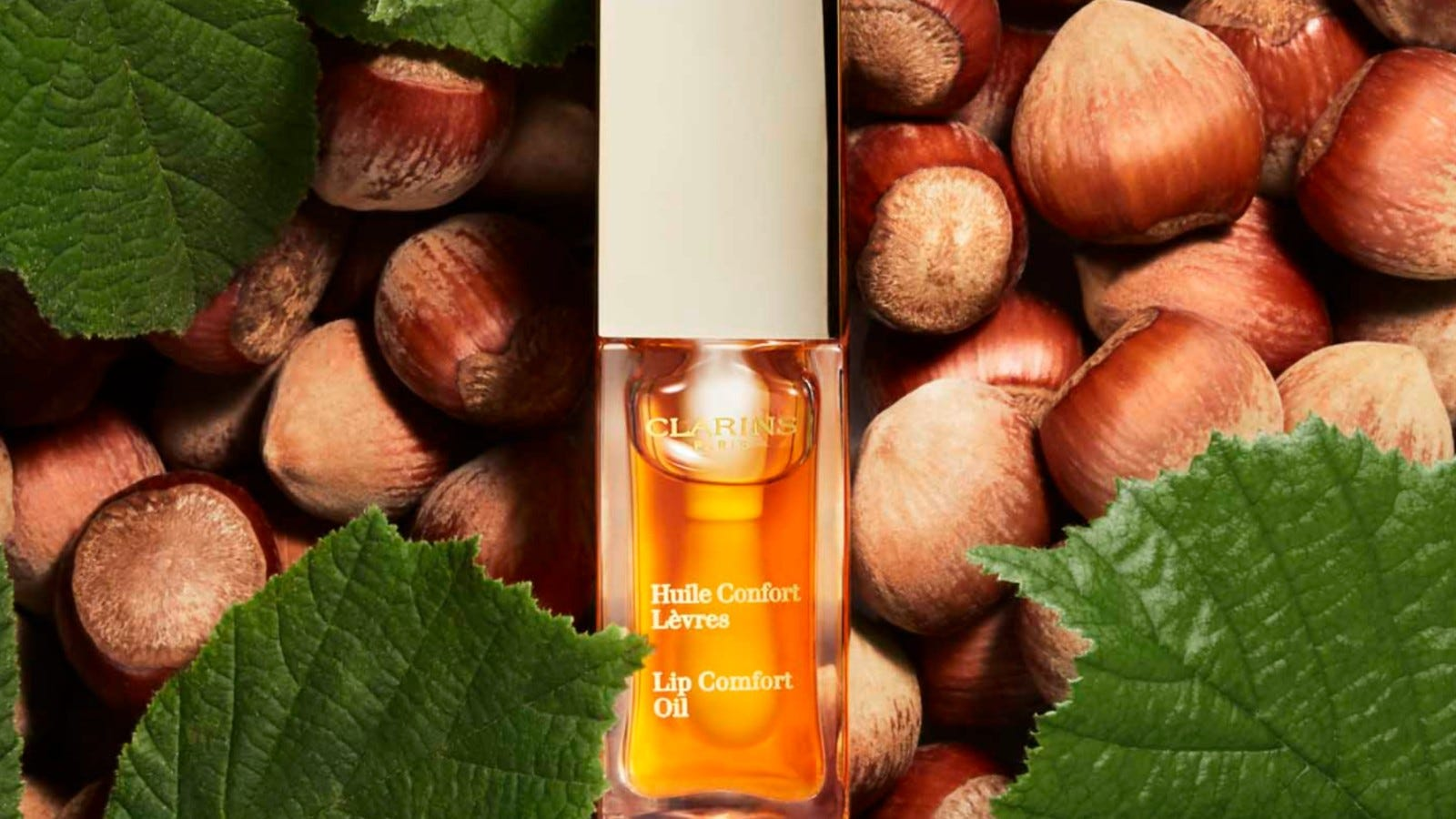 orange Clarins lip oil on a background of leaves and hazelnuts