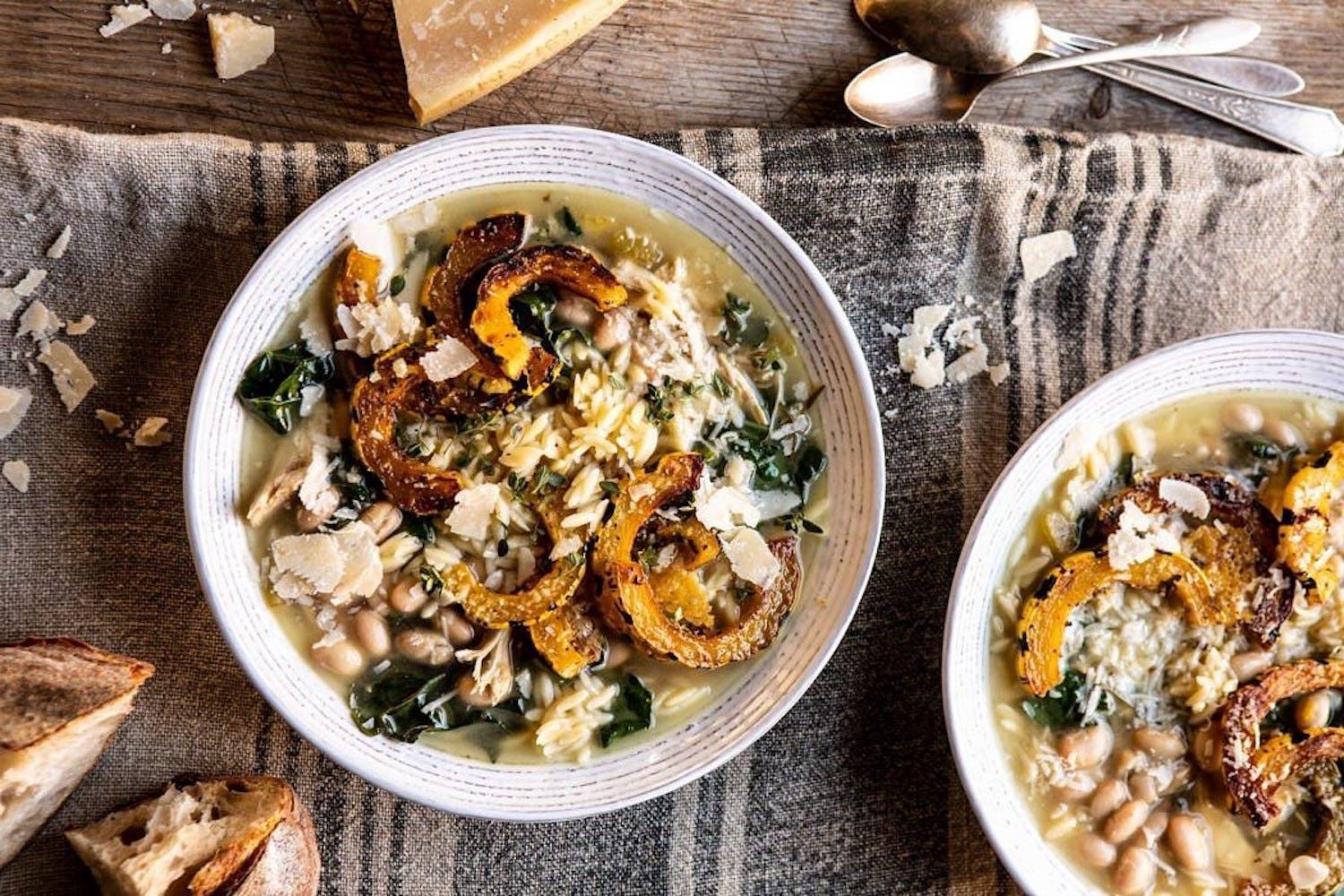 A bowl of chicken white bean soup with squash slices, sitting on a striped kitchen towel