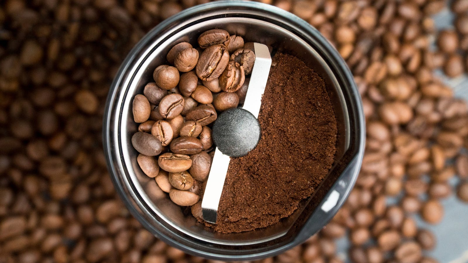 A blade coffee grinder half filled with beans, and the other half filled with ground coffee with a lot of coffee beans in the background.