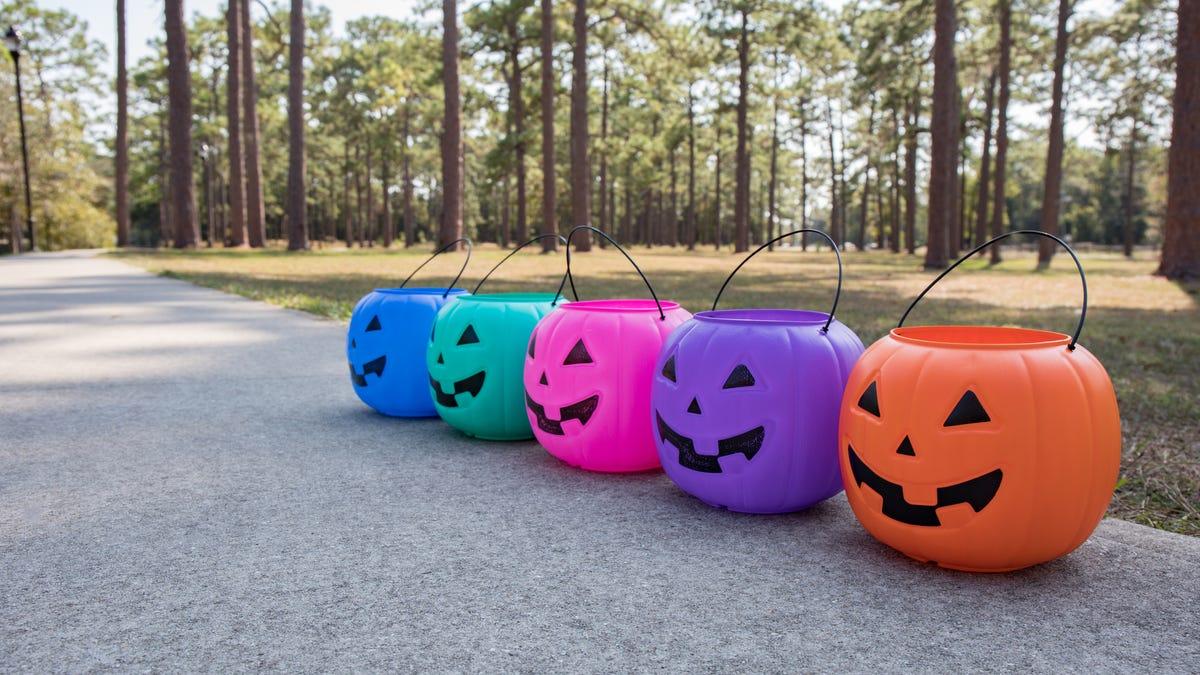 A row of multi-colored jack o'lantern buckets sits on a sidewalk.