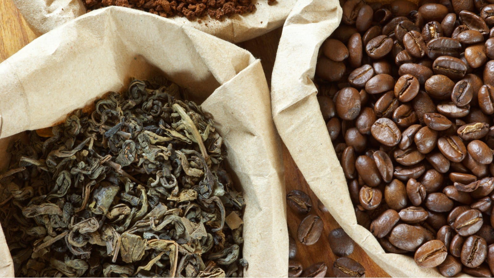 Two paper bags; one filled with tea leaves and the other filled with coffee beans.