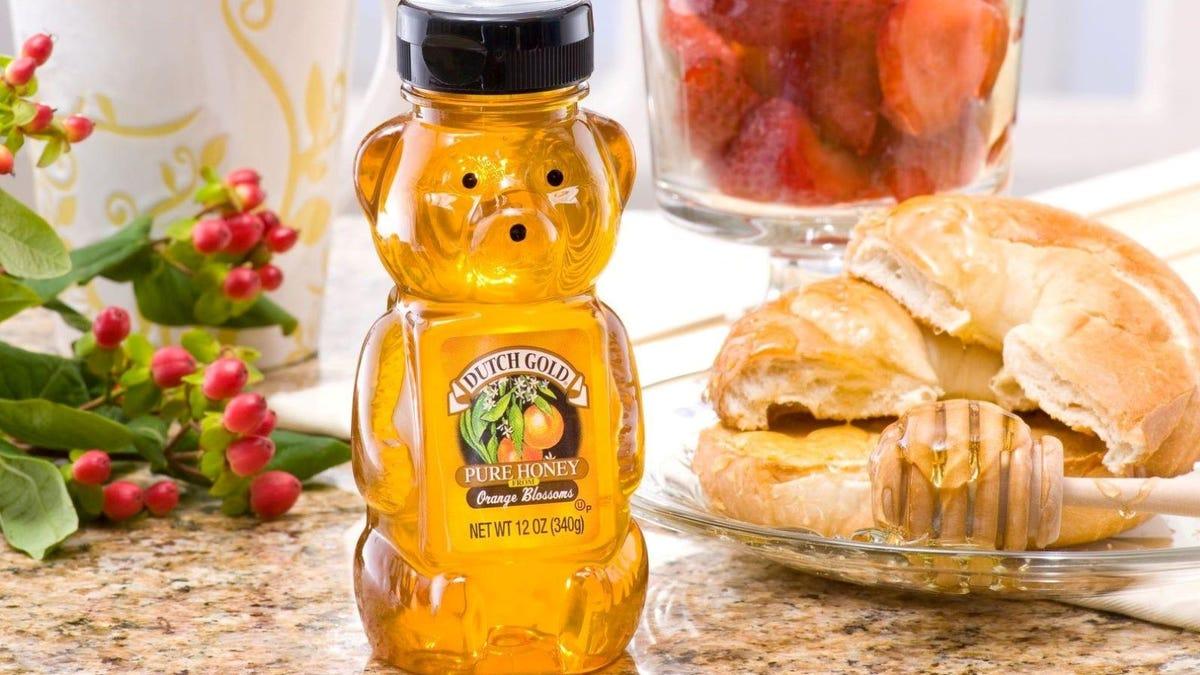 A Dutch Gold Honey Bear sitting next croissants on a plate.