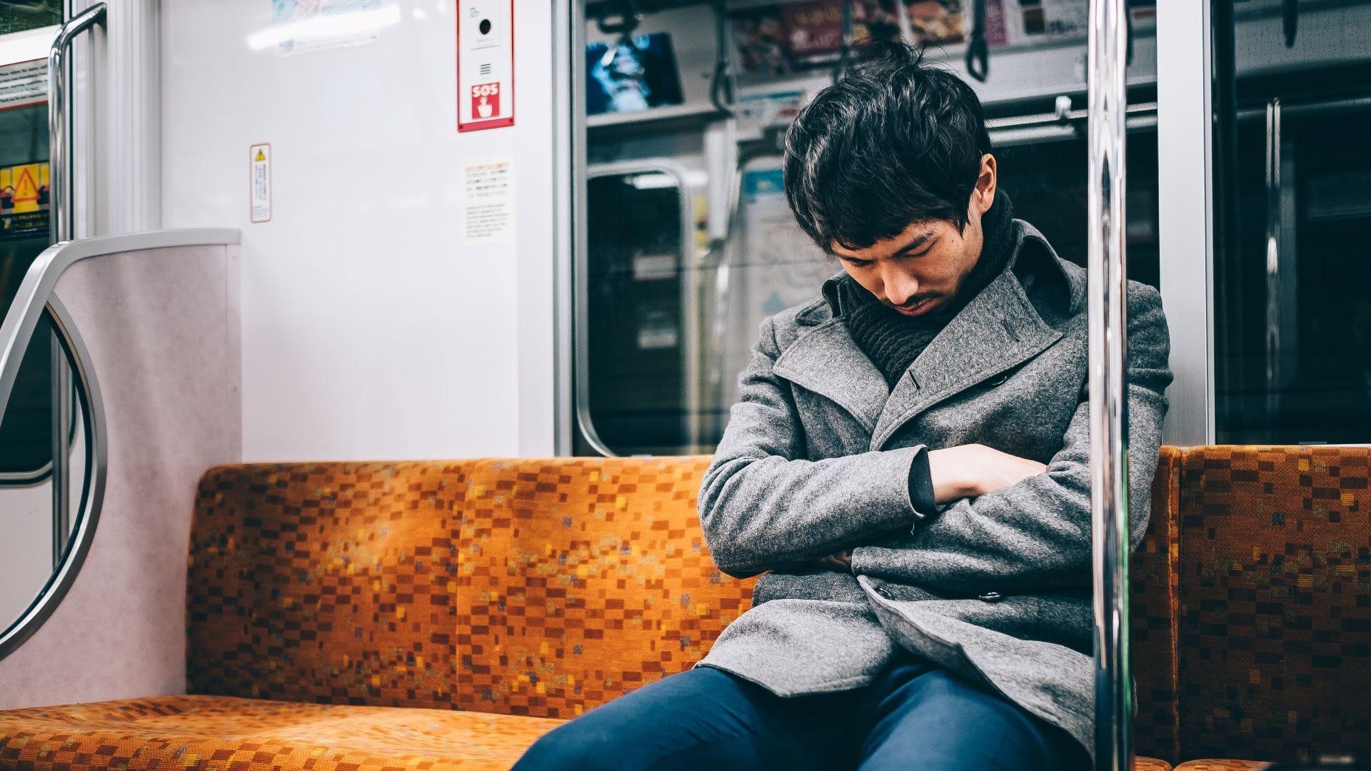 A Japanese man asleep on a train.